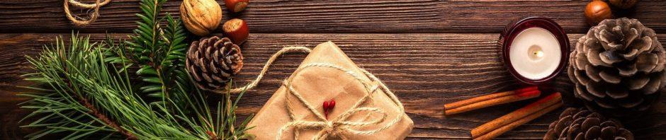 Weihnachtsdekoration: Ein paar Tannenzweige, ein verpacktes Geschenk, eine Kerze und Zimtstangen.