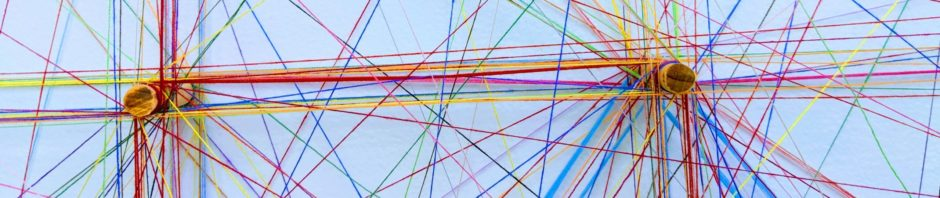 Zwei Schrauben in einer weißen Wand. Zwischen den Schrauben und weiteren Punkten außerhalb des Bildes spannen sich zahlreiche Fäden in verschiedenen Farben und bilden ein buntes Netzwerk.